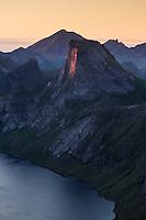 Last light illuminates vertical face of Segltind rising above Kjerkfjord, Moskenesøy, Lofoten Islands, Norway