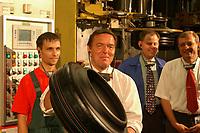 15 AUG 2001, FUERSTENWALDE/GERMANY:<br /> Gerhard Schroeder, SPD, Bundeskanzler, besucht das die Pneumant GmbH und laesst sich im Rahmen eines Betriebsrundganges die Reifenherstellung von einem Auszubildenden erklaeren, hier mit einem Reifen Rohling, Pneumant GmbH<br /> IMAGE: 20010815-01-015.jpg<br /> KEYWORDS: Gerhard Schröder, Kanzlerreise, Azubi, Auszubildender, Fürstenwalde, reifen, Autoreifen