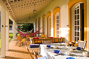 Private home in Parati Brazil. Back terrace, overlooking the sea, with wooden table and chairs. Decorated with cushions.