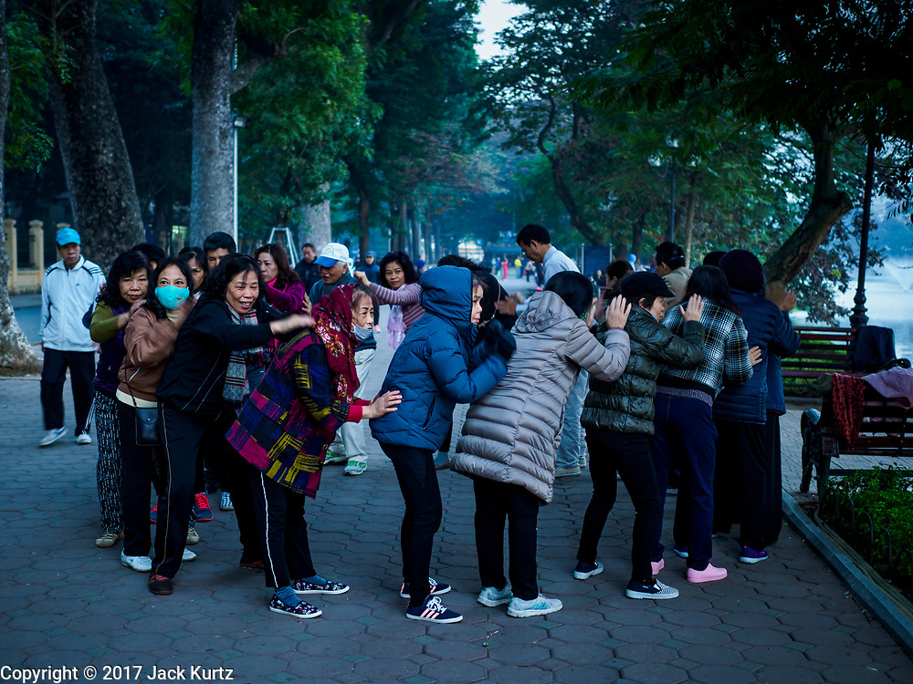26 DECEMBER 2017 - HANOI, VIETNAM: People finish their exercise sessions with massage and muscle loosening at Hoan Kiem Lake, in the Old Quarter of Hanoi. Thousands of Vietnamese people line the lake front in the early hours of the morning to perform tai chi and other low impact aerobic workouts.     PHOTO BY JACK KURTZ