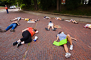 "30 JULY 2020 - DES MOINES, IOWA: People lay in the road on Forest Drive in front of the Governor's Mansion during a ""die in."" About 45 high school students from across Des Moines marched from downtown to the Governor's Mansion to protest Iowa Governor Kim Reynolds' proclamation ordering Iowa schools to reopen to in person classes despite the COVID-19 pandemic. The students stood in front of the mansion and chanted before staging a ""die  in"" in the street. The Governor's order mandates in person instruction rather than on line or a mix of on line and in person. Several school districts have indicated that they will disregard the Governor's orders and reopen with a hybrid system or mostly on line. The Governor will allow districts to apply for a waiver if the Coronavirus (SARS-CoV-2) infection rate is more than 15% in their community.     PHOTO BY JACK KURTZ"