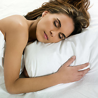 beautiful  woman sleeping on a white bed