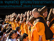 """02 JANUARY 2016 - KHLONG LUANG, PATHUM THANI, THAILAND: Monks from the Dhammakaya sect start the pilgrimage at Wat Phra Dhammakaya on the first day of the 5th annual Dhammachai Dhutanaga (a dhutanga is a """"wandering"""" and translated as pilgrimage). More than 1,300 monks are participating pilgrimage through central Thailand. The purpose of the pilgrimage is to pay homage to the Buddha, preserve Buddhist culture, welcome the new year, and """"develop virtuous Buddhist youth leaders."""" Wat Phra Dhammakaya is the largest Buddhist temple in Thailand and the center of the Dhammakaya movement, a Buddhist sect founded in the 1970s. The monks are using busses on some parts of the pilgrimage this year after complaints about traffic jams caused by the monks walking along main highways.          PHOTO BY JACK KURTZ"""