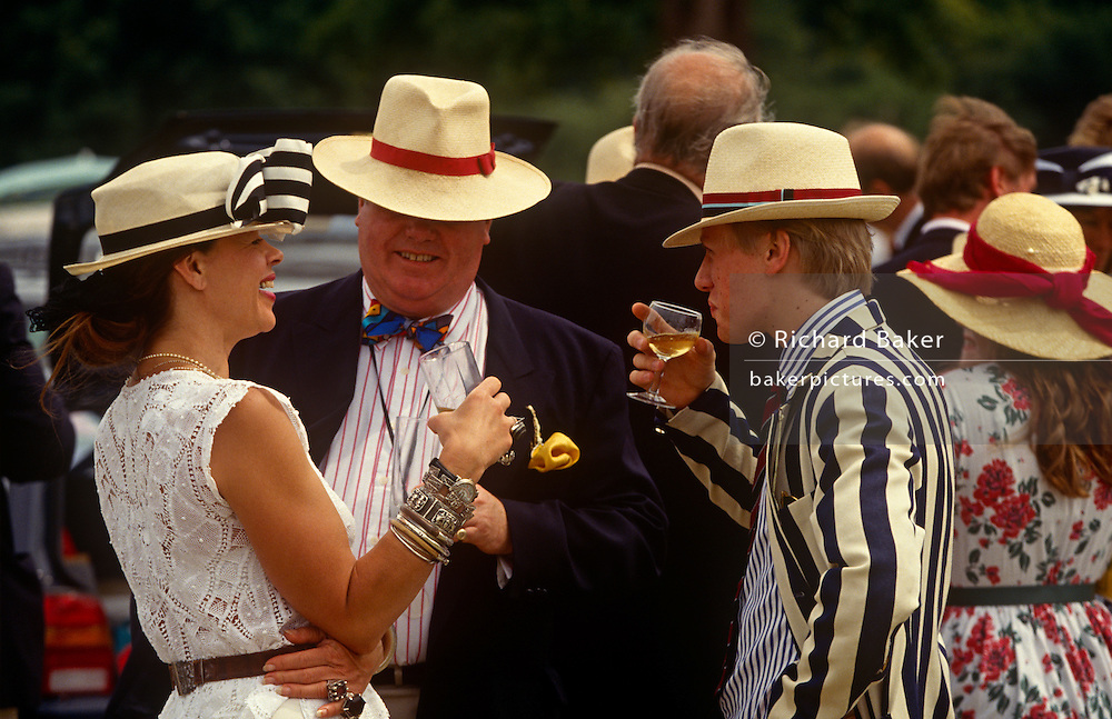 Wealthy friends enjoy bubbly and fizz during the annual Henley Regatta on a particularly hot afternoon at the Henley boat races, England. Dressed in quintessentially English blazers and English jackets and dresses, they are in jovial spirits during this annual festival of high-society, serious rowing and general clowning around on the rural Thames. In 1829 a boat race challenge was held between teams representing the universities of Oxford and Cambridge. The venue chosen was a straight stretch of the Thames at the small town of Henley-on-Thames. Now held July and is one of the main dates on the sporting calendar and social season for the hoi polloi
