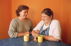 Mother and daughter sitting at kitchen table talking,