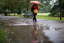 © Licensed to London News Pictures. 27/09/2021. London, UK. A woman shelters under an umbrella as she walks past a large puddle during a rain shower in Greenwich Park. Rain showers are forecasted to continue in parts of London and South East England for the rest of the week.  Photo credit: George Cracknell Wright/LNP