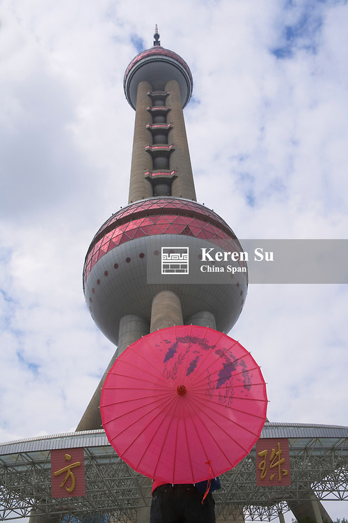 Girl with red umbrella with Oriental Pearl TV Tower, Shanghai, China