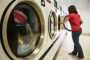 A young British woman loads clothes into a washing machine in a launderette in Wadebridge, Cornwall, UK. The energy for the launderette is sourced from roof solar panels and is part of a scheme to make this town the first to be powered by renewable sources in the UK.