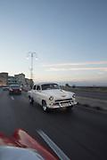Vintage car driving along Malecon road at dawn, Havana, Cuba