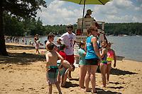 Lifeguard Seth Valpey talks with beachgoers Friday morning at Gilford Beach.  (Karen Bobotas/for the Laconia Daily Sun)