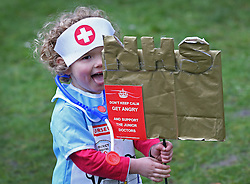 © Licensed to London News Pictures. 09/01/2016. London, UK. Two year old Annabel Pickstone holds an NHS placard during a rally against the proposed cancellation of bursaries for nurses hoping to train for work in the NHS.  Photo credit: Peter Macdiarmid/LNP