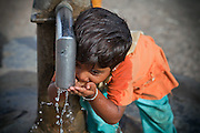 A young girl is drinking contaminated water from a hand-pump near the abandoned Union Carbide (now DOW Chemical) industrial complex in Bhopal, Madhya Pradesh, India, site of the infamous 1984 gas disaster.