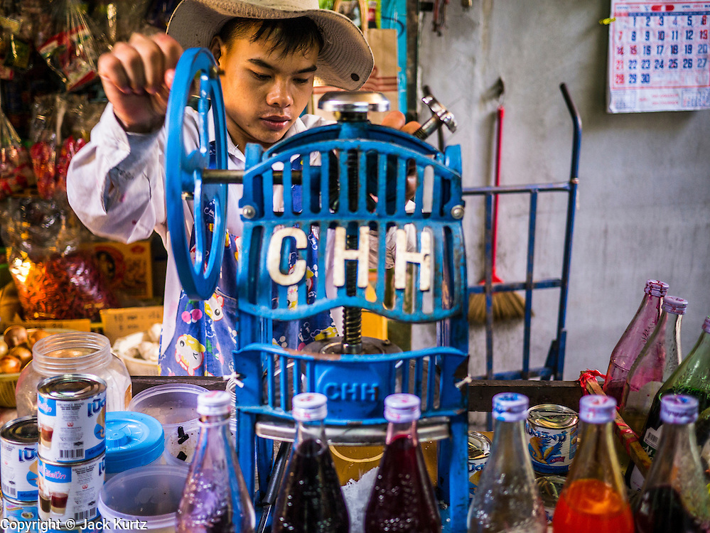 """20 APRIL 2013 - BANGKOK, THAILAND:   A """"slushy"""" vendor makes crushed iced drinks in Talat Noi (Talat means Market, Noi means Small. Literally Small Market). The Talat Noi neighborhood in Bangkok started as a blacksmith's quarter. As cars and buses replaced horse and buggy, the blacksmiths became mechanics and now the area is lined with car mechanics' shops. It is one the last neighborhoods in Bangkok that still has some original shophouses and pre World War II architecture. It is also home to a  Teo Chew Chinese emigrant community.   PHOTO BY JACK KURTZ"""