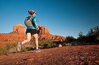 A young woman runs on a trail below Cathedral Rock in Sedona, Arizona.