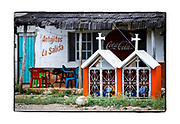 SHOT 2/19/19 11:58:54 AM - An identical pair of small roadside capillas mirror each other in front of a restaurant in the small town of Hopelchen, Mexico. Hopelchén is a city in the Mexican state of Campeche. It is situated inland in the north of the state. It serves as the municipal seat for the surrounding Hopelchén Municipality. In 2010, Hopelchén had a population of 7,295. It is also home to a large Mennonite community. The capillas are often dedicated to certain patron saints or the memory of someone that has died at or near the site. Common throughout the backroads and secondary highways of Mexico they often contain prayer candles, pictures, personal artifacts or handwritten notes. (Photo by Marc Piscotty / © 2019)