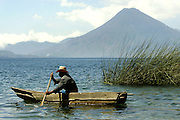 A fisherman makes his way out onto Lake Atitlan in Santa Catarina Palopo, Guatemala.  The back ground San Pedro volcano reaches for the clouds.