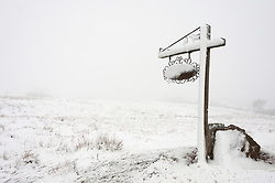 © Licensed to London News Pictures. 04/04/2019. Builth Wells, Powys, Wales, UK. A farm sign is blasted with snow from the blizzard conditions on the Mynydd Epynt range between Builth Wells and Brecon in Powys, UK. Photo credit: Graham M. Lawrence/LNP