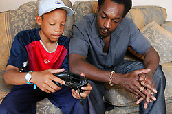 Young teenager sitting with his father; showing him his computer game,