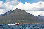 Rigid inflatable tourist sealwatching boat trip, with The Cuillins mountains behind, on visit to Isle of Canna part of the Inner Hebrides and Western Isles in West Coast of Scotland