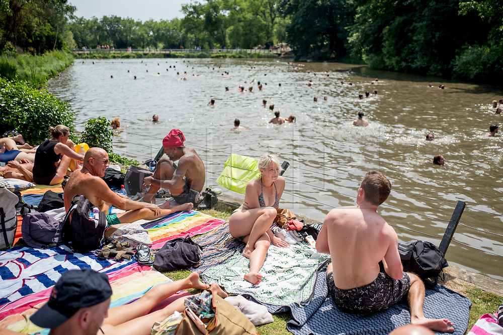 © Licensed to London News Pictures. 01/07/2018. London, UK. People sunbathe in Hampstead Heath Mixed Bathing Pond in north London on Sunday, July 1, 2018 as heatwave has reached 31C and is set to continue into the next week and the unusually high temperatures look set to remain until the week after next. Photo credit: Tolga Akmen/LNP