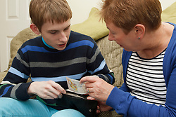 Young man with autism with mother sorting money. Cleared for Mental Health issues.