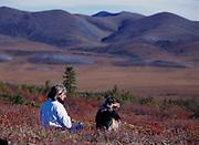 Randi Hirschmann with Australian Shepherd Mattie enjoying tundra at the Arctic Circle Overlook, Richardson Mountains beyond, Demptster Highway, Yukon Territory, Canada.