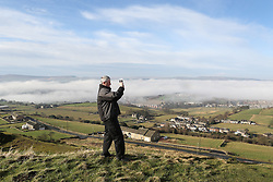 © Licensed to London News Pictures. 06/02/2017. Huddersfield, UK. A man photographs the spectacular views as thick banks of fog covering Huddersfield on a cold February morning in West Yorkshire. Forecaster are predicting heavy rain this week but none was in sight here as the sun began to shine and burn through the dense fog. Photo credit : Ian Hinchliffe/LNP