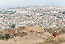 Man watching sunset on overlook with view of Fes al Bali medina, Fes, Morocco