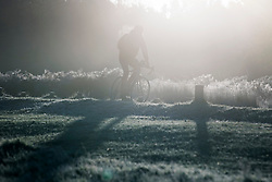 © Licensed to London News Pictures. 04/11/2020. London, UK. A man cycles through a frost covered landscape at sunrise in Richmond Park, south west London on a cold Autumn morning. Photo credit: Ben Cawthra/LNP