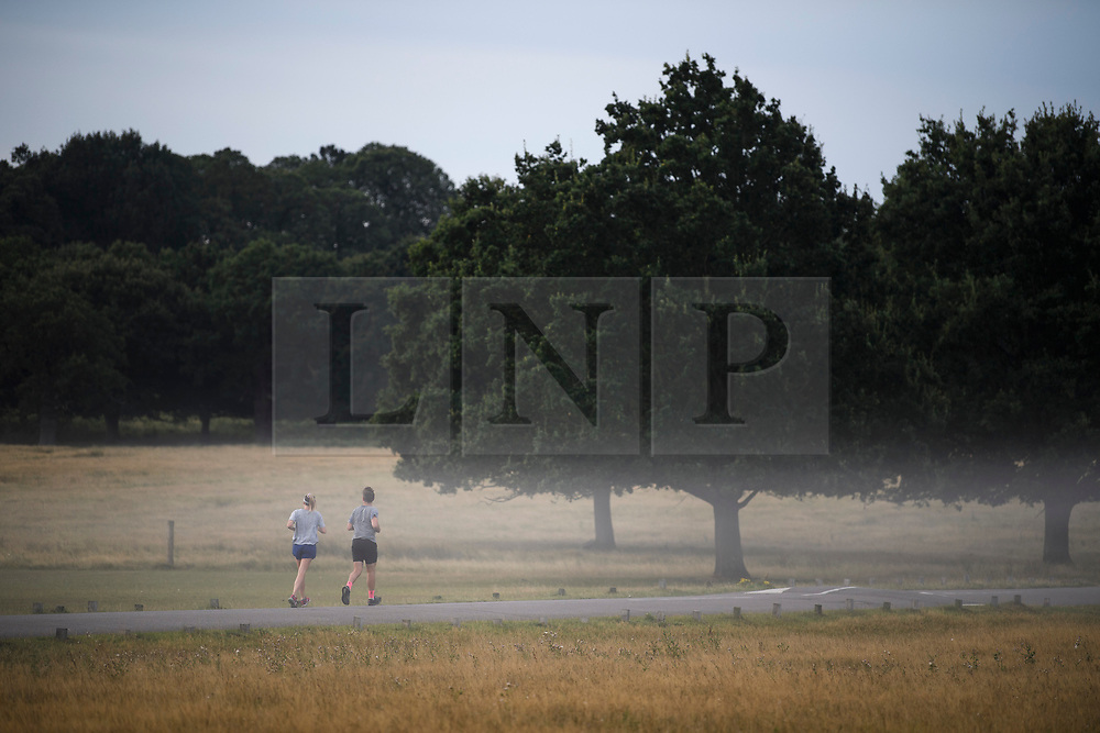 © Licensed to London News Pictures. 01/09/2019. London, UK. Two people jogging through a mist covered landscape at first light in Richmond Park on the first day of meteorological autumn. Photo credit: Ben Cawthra/LNP