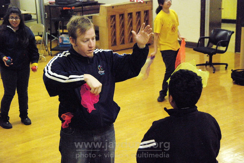 """USA, Chicago, IL, December 12, 2009.  Paul Lopez demonstrates some of the finer points of juggling. Students in the """"At-Risk After School Program"""" at Maria Saucedo Scholastic Academy receive training in basic physics principles through an innovative new program called """"Circus Galactica"""" put on by Pros Arts, a non-profit organization founded in 1978 by professional artists dedicated to the Pilsen/Little Village communities. In a residency that directly integrates science and art, veteran circus performers Douglas Grew and Paul Lopez bring the importance of """"balance, focus and presentation"""" into hands-on lessons about gravity, inertia, and the dynamics of objects in motion. Photo for Hoy by Jay Dunn."""
