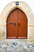 Typical arched brown front door with wrought iron studs and doorway of a house in a cobble stone street in Evora, Portugal