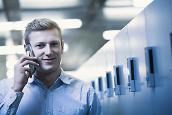 Portrait of young man talking on mobile phone in locker room, Freiburg im Breisgau, Baden-Wuerttemberg, Germany