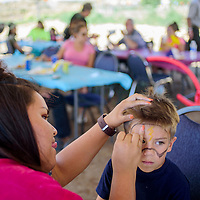 Ephraim Otero, right, has his face painted by Kne-bah Montaño during the Garden Party fundraiser Saturday at the Community Pantry in Gallup.