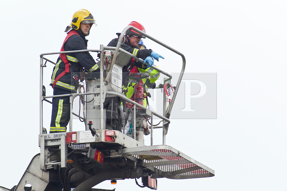 © Licensed to London News Pictures. 27/06/2012. Oldham , UK . A large explosion , believed to be caused by gas , has brought down at least one house in an Oldham terrace . A fire crew uses a hydraulic lift to examine damage to the rooves of houses surrounding the site . Photo credit : Joel Goodman/LNP