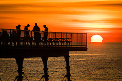 © Licenced to London News Pictures<br /> <br /> 24 June 2018 . Aberystwyth Wales UK<br /> <br /> UK Weather:  People silhouetted standing at the end of the pier in Aberystwyth as the sun sets dramatically over Cardigan Bay  at the end of yet another scorchingly hot  and sunny day.<br /> <br /> The UK is heading  into a mini heatwave, with temperatures forecast to hit 29º or 30º Celsius by the middle of the week<br /> <br /> photo credit Keith Morris/LNP