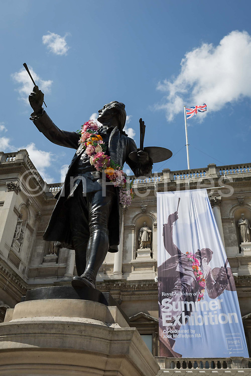 The statue of Sir Joshua Reynolds outside the Royal Academy in Piccadilly during the Summer Exhibition, on 5th August 2019, in London, England. This is a new cast of the original that was first exhibited outside the RA in 1904 and is an allegory of the human need for new challenges, of our instinct to always be scanning the horizon and the future. Sir Joshuas statue stands in the Annenberg Courtyard of Burlington House.