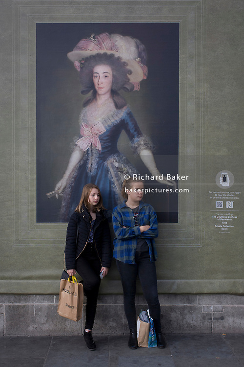 Two young woman listen to a busker beneath a portrait of the Countess-Duchess of Benavente by Goya (1885), sponsored by Credit Suisse and advertised on a construction hoarding outside the National Portrait Gallery.