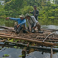 An Indian guides paddles photographers on a raft on a remote lake in Peru's Amazon Jungle. Also in the water are Pirana, Caiman, snakes & other hazards.