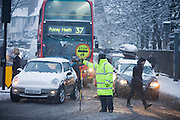 Rush-hour traffic is stopped at a road junction in Dulwich Village, South London, as pedestrians are helped across the snowy road by a Southwark council lollipop man.
