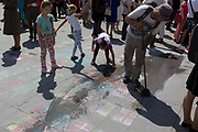 A street busker wipes away the chalk images of international flags that he's drawn on the pavement in Trafalgar Square, on 9th May 2018, in London, England.