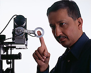 Dr. Mandayam Srinivasan, founder of the MIT Touch Lab with a device that measures the pressure sensitivity of the fingertip.