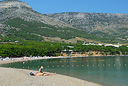 Sunbakers on beach at Zlatni Rat, near Bol, island of Brac, Croatia