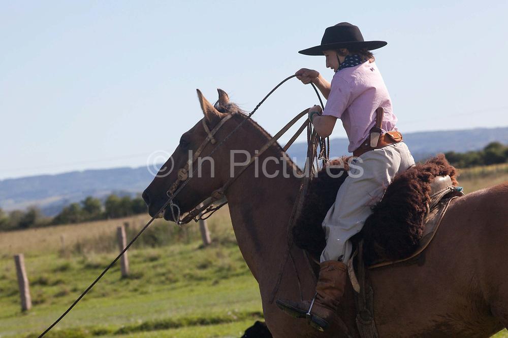 Young boy Gaucho cowboy Brazilian riding a horse. Working Gaucho Fazenda in Rio Grande do Sul, Brazil.