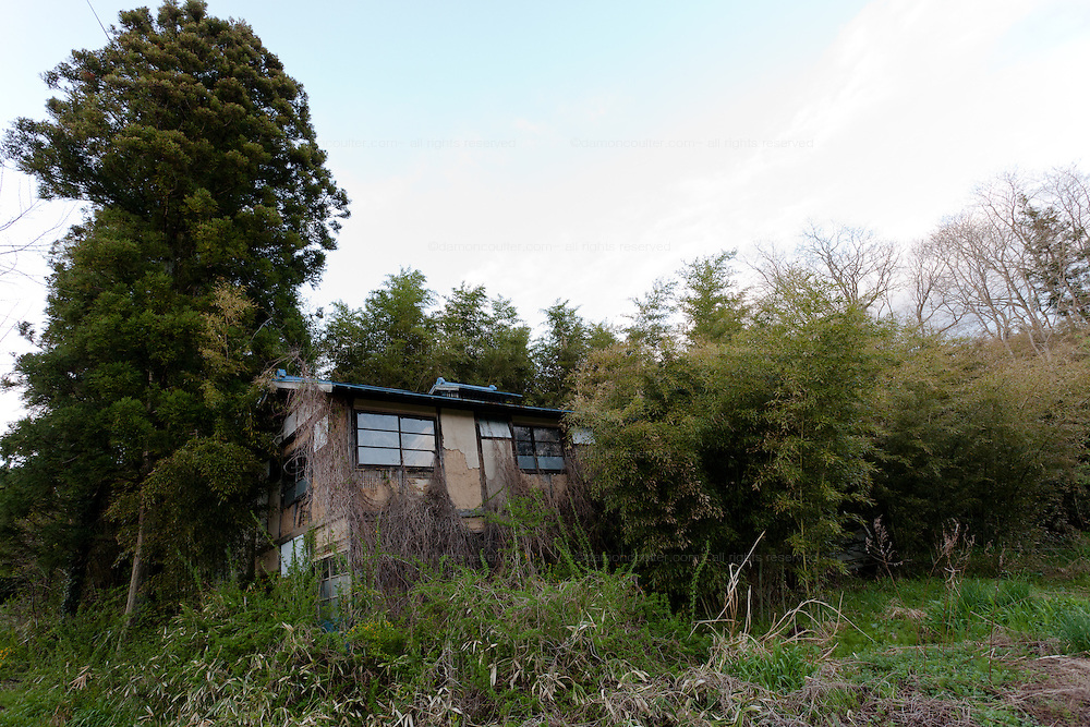 Vegetation in encroaching on an empty house the abandoned village of Tsushima in Fukushima, Japan. Friday May 4th 2012. After the explosions at the Daichi nuclear plant caused by the March 11th 2011 earthquake and tsunami, High levels of radioactive contamination in this village have made it uninhabitable.