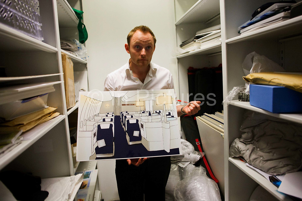 """In an office stock room, an archivist in British Airways' Customer Experiences Divition shows some conceptual design ideas for future Business Class cabin layouts, seen at the airline's corporate headquarters at Waterside at Harmondsworth near Heathrow Airport. Having listened to their passengers' ideas for what they'd like to experience in their long-haul cabins, BA regularly come up with ways to make the flight for premium users a reason to become loyal fare-payers. From writer Alain de Botton's book project """"A Week at the Airport: A Heathrow Diary"""" (2009)."""