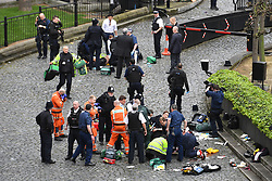 Emergency services attend a man (top) and a police officer (bottom) outside the Palace of Westminster, London, after policeman was stabbed and his apparent attacker shot by officers in a major security incident at the Houses of Parliament.