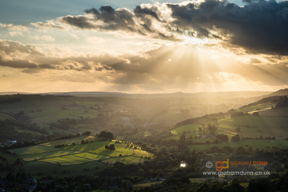 Crepuscular rays erupt from the sky and illuminate patches of the landscape around Calver in Derbyshire. A classic summer scene in the Peak District captured from Curbar Edge. The glint of light in the foreground is from the sun reflecting in the River Derwent as it passes under Calver Bridge.