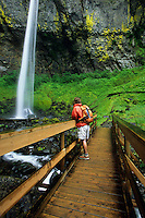 A young man admires a waterfall while hiking in the Columbia River Gorge, Oregon.