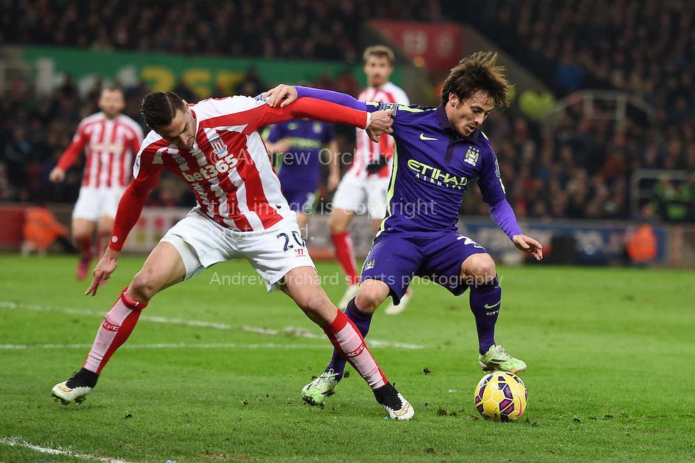 Geoff Cameron of Stoke city (l) tackles David Silva of Manchester city. Barclays Premier League match, Stoke city v Manchester city at the Britannia Stadium in Stoke on Trent , Staffs on Wed 11th Feb 2015.<br /> pic by Andrew Orchard, Andrew Orchard sports photography.
